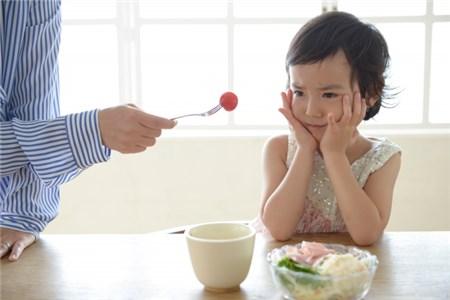 トマトを食べさせられそうになっている女の子