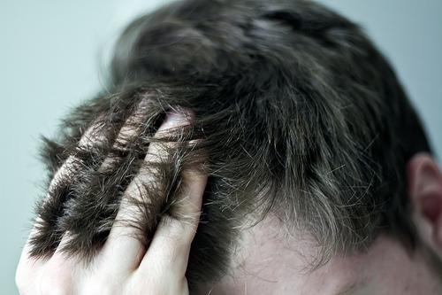 イライラして髪を触っている画像