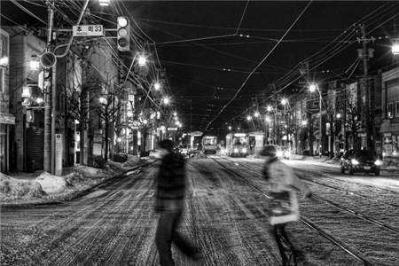 夜の街を小走りに行く男女