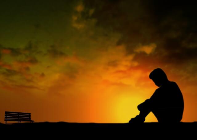 夕暮れの中、座り込む男性のシルエット