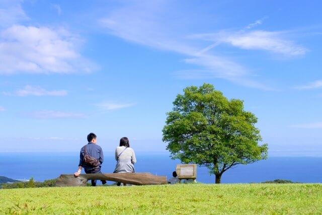 海の見えるところでピクニックデートをするカップル