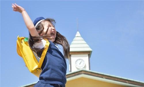 学校の校庭で飛び跳ねる女の子