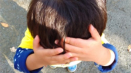 顔を押さえて泣く子ども