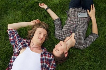 草地に寝そべる男女カップル