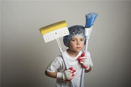 掃除用具を抱える外国人の子供