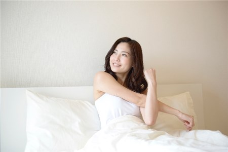 寝起きに腕をストレッチする若い女性
