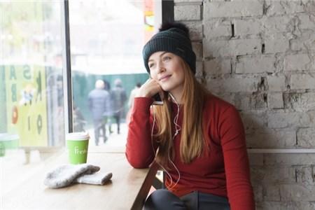 カフェの窓際で読書とコーヒーを楽しむ白人女性