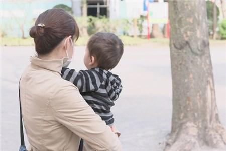 公園で赤ちゃんをだっこするお母さん