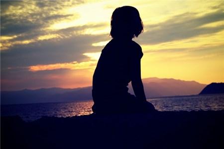 黄昏時に物憂げに考え事をする女性のシルエット