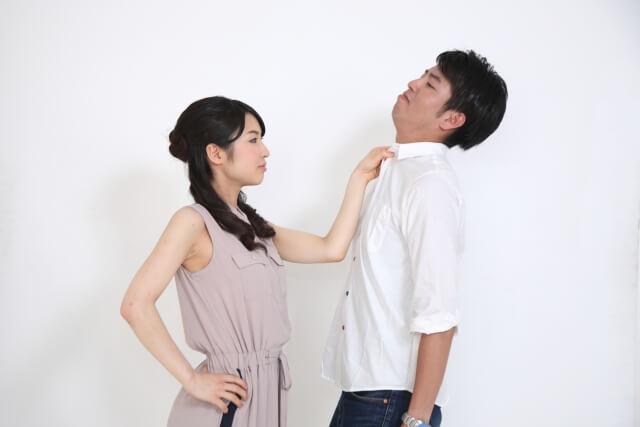 女性に首根っこをつかまれる男性