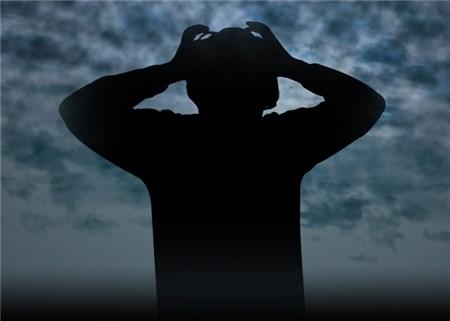 頭を抱える男性のシルエット